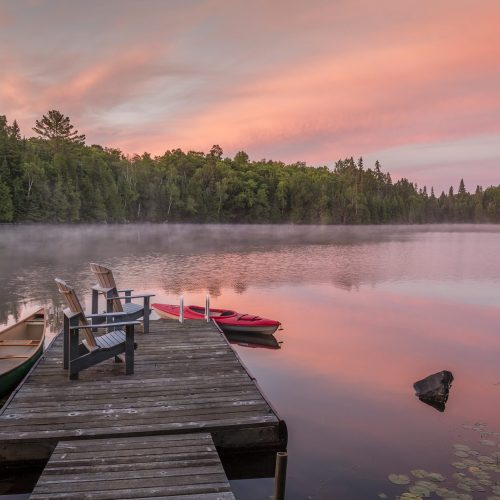 Canoe and kayak moored to a cottage dock at dawn - Ontario, Canada